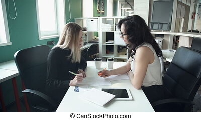 Two business women discuss working issues in office using...