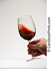 Hand shaking red wine glass isolated on white background