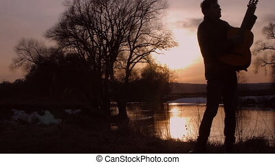 The man playing the guitar at sunset (silhouette) - The man...