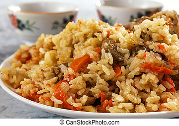 Friable pilaf with meat on a background of cups with tea....