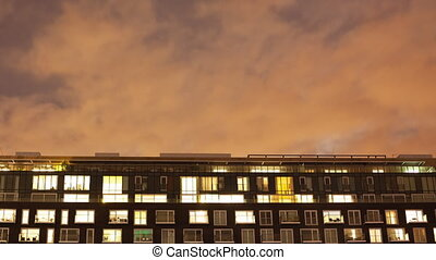 Time-lapse of the exterior of a modern apartment block at night