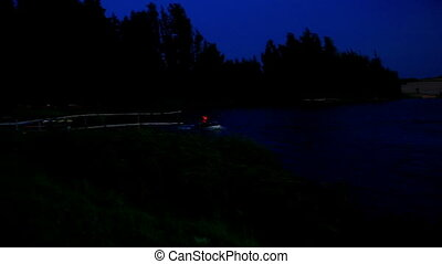 Water Scooter Races along Dark Lake under Black Sky at Night...