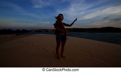 Silhouette Mother Holds Small Girl in Arms Photos Lake at...