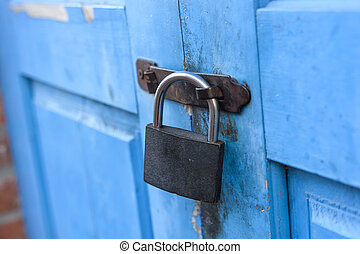 Hanging metal padlock - Blue wooden door of old abandoned...