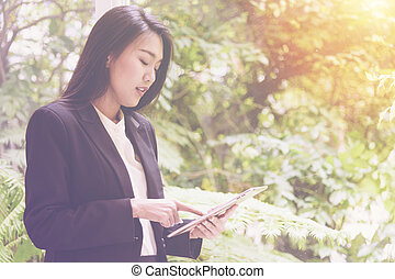 Elegant young business woman using tablet leaning stand by the window for relax, looking at screen
