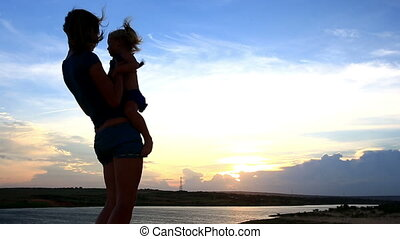 Close Silhouette Mother Lifts Small Girl in Arms by Lake at...