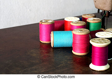 colorful bobbins of thread on sewing machine