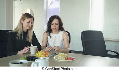 Two women have coffee break, discuss manicure indoor....