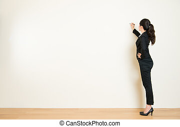 Business woman writing something on white wall