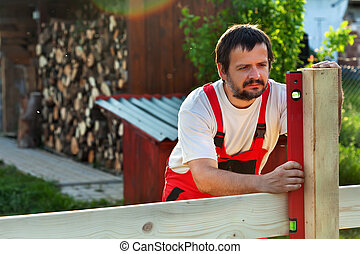 Man building a wooden fence - checking the posts with a level