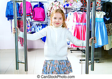 holiday girls shopping - Happy little girl in a clothing...