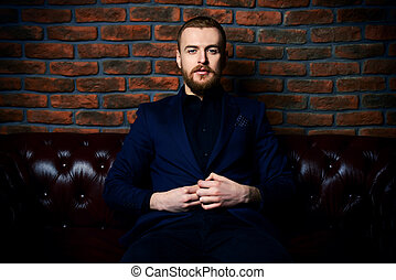 calm and confident - Imposing well dressed man sitting on a...