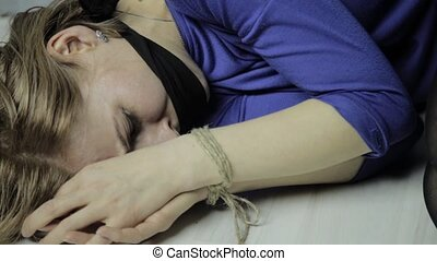 frightened cries girl gagged, lies on the floor with tied hands. kidnapping and violence