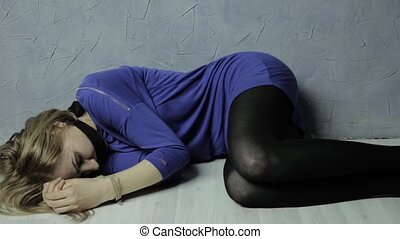 frightened girl gagged lies on the floor with tied hands,...