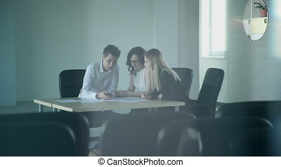 In an empty conference room, three employees work overtime for papers