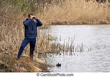 Man watching birds by the lake - Man watching birds through...