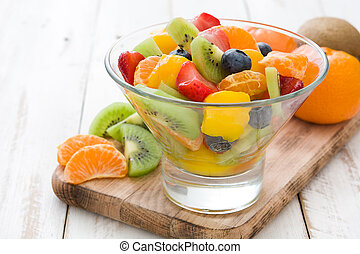 Fruit salad in crystal bowl on white wooden table.