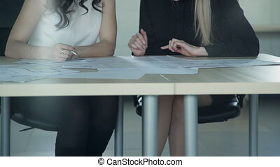 Two women discuss something base on documents on board...