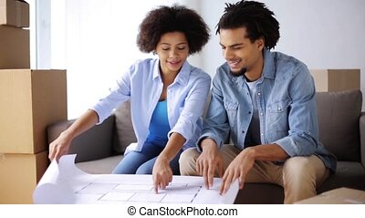 happy couple with blueprint and boxes at new home - people,...