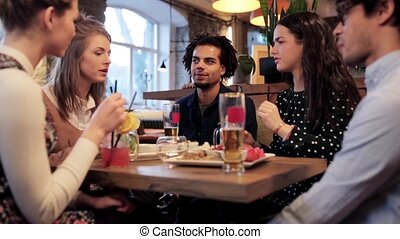 happy friends eating and drinking at bar or cafe - leisure,...