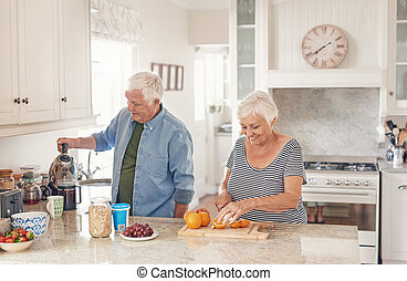 Happy senior couple preaparing a healthy breakfast in their kitchen