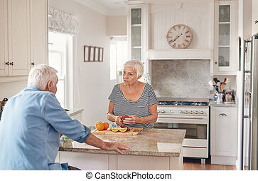 Senior couple talking together while preparing breakfast in their kitchen