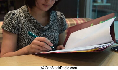 Woman busy with paperwork in cafe - Businesswoman looking...