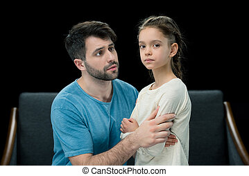 portrait of father holding pensive little daughter on black