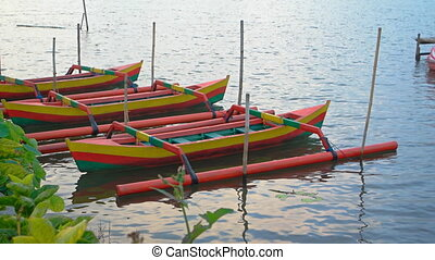 Traditional wooden boats for tourists on Danau Beratan lake....