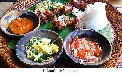 Eating of Urutan Banjar - pork sausage - tradition Balinese...