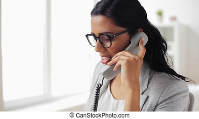 businesswoman with pad calling on phone at office -...