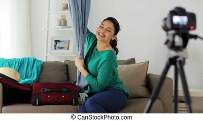 woman with travel bag recording video at home - blogging,...