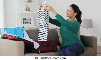 woman packing clothes to travel bag at home - tourism,...
