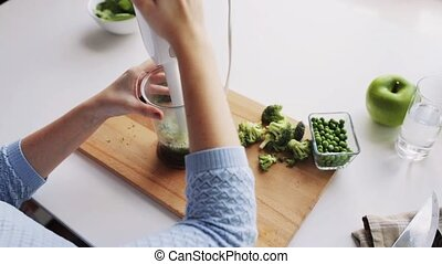 woman with blender cooking vegetable food at home - solid...