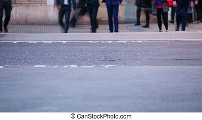 Time-lapse of Pedestrians crossing a road at dusk, London, England