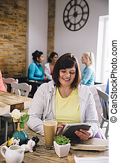 Working In A Cafe - Mature woman is sitting in a cafe using...