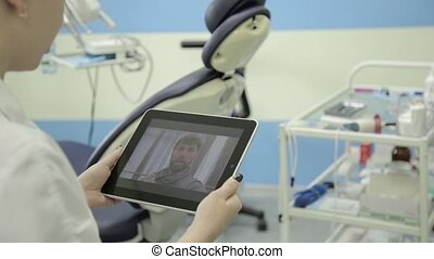 senior patient video chatting with dentist on pc tablet....