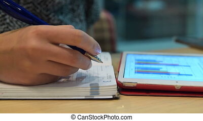 Business woman taking notes and using touch pad - Close-up...