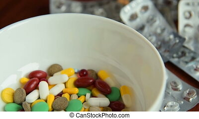 Bowl with pills and empty blisters - Close-up shot of a bowl...