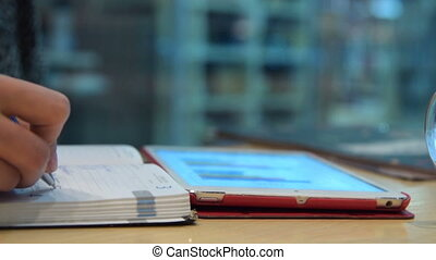 Business woman making notes and using digital tablet -...