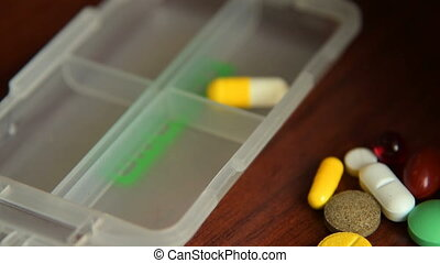 Placing medicines into the pill case - Close-up shot of...