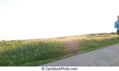 Young woman runner running on sunrise road. Fitness concept...