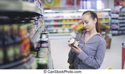 Girl looks products at grocery store - girl with food in...