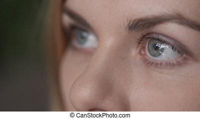 Close up view on eyes of blonde woman looking on big screen....