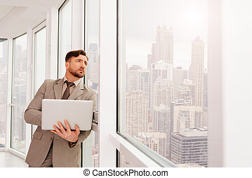 Serious businesssman leaning on the office window -...