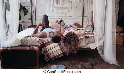 Multiracial couple lying on bed, listening music on...