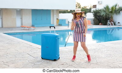Travel vacation concept. Young woman near swimming pool with...