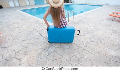 Travel vacation concept. Young woman near swimming pool