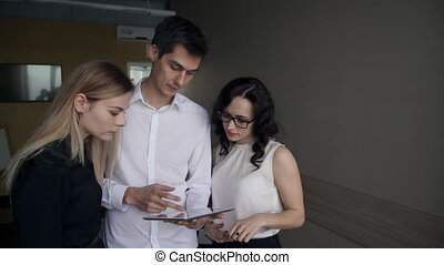 Three office workers look to digital tablet screen inside...