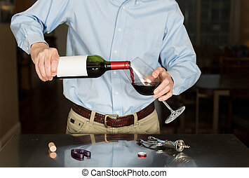 Senior man pouring from wine bottle with blank label -...
